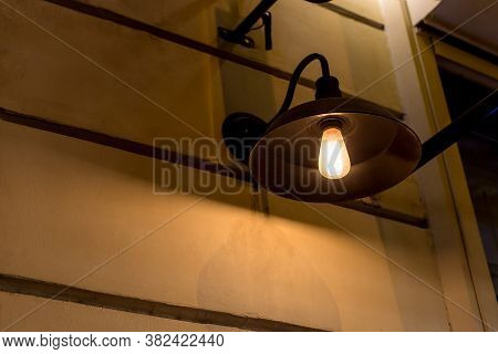Decorative Black Iron Lantern In Loft Style With Edison Bulb On The Wall Of Facade Building The City