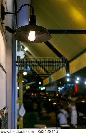 Decorative Black Iron Lantern In Loft Style With Edison Bulb On The Wall Of Facade Street Cafe With