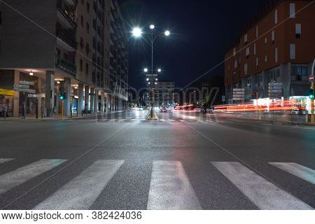 Timelapse View Of Traffic At An Urban Night Intersection. Urban Movement In The Italian City In The