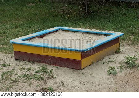 Colored Square Wooden Sandbox With White Sand Stands On The Ground And Green Grass In The Playground
