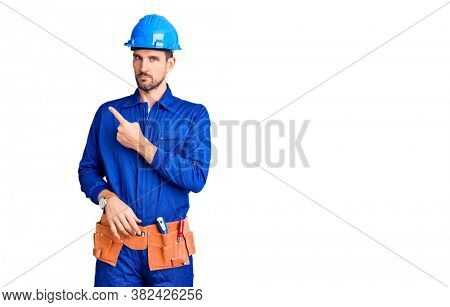 Young handsome man wearing worker uniform and hardhat pointing to the eye watching you gesture, suspicious expression