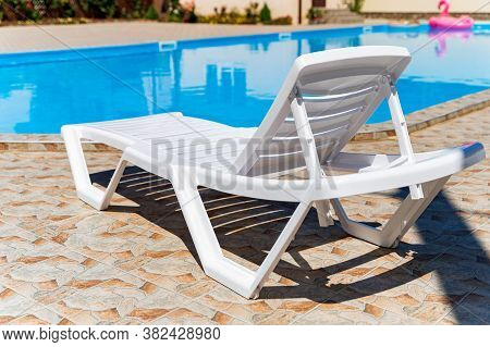 Empty Plastic White Deck Chairs Near The Swimming Pool