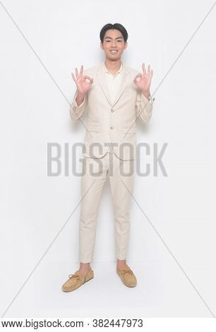 Full body young handsome man wearing in beige suit with polo shirt and beige pants and brown shoes with shows the OK gesture sign
