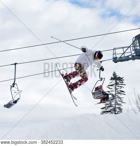 Alpine Skier In White Winter Jacket And Helmet Skiing Downhill With Beautiful Cloudy Sky And Ski Lif