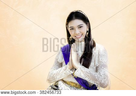 Asian Woman In Thai Traditional Vintage Costume Siting And Greeting Action On Brown Background. Gree