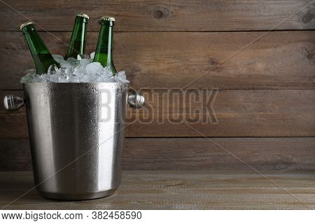 Metal Bucket With Beer And Ice Cubes On Wooden Table. Space For Text