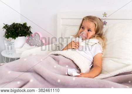 Little Girl Makes Inhalation With A Nebulizer In The House Lying In Bed In White Room. Child Asthma