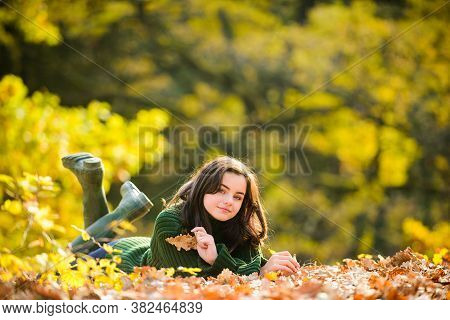 Smiling Teenage Girl Lying On Yellow Leaves In Autumn. Autumn Teenager On Leafs