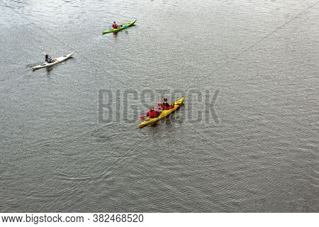 Four People On Three Kayaks Are Floating On A Calm River. Several People Are Paddling A Kayak. Kayak