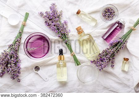 Lavender Oils Serum And Lavender Flowers On White Fabric. Skincare Cosmetics Products. Set Natural S