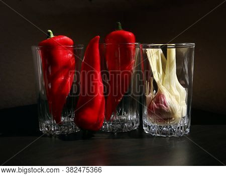 Still Life With Red Ramiro Peppers And Garlic Bulb In The Vintage Glass Beakers Against A Low Key Ba