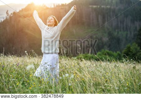 Happy woman enjoying stay on the green grass on the forest peak of mountain. Fresh air, Travel, Summer, Fall, Holidays, Journey, Trip, Lifestyle.