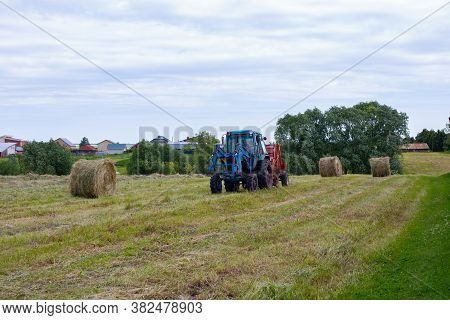 Rybushkino Village, Russia - July 1, 2020: Blue Tractor Collects Large Round Rolls Of Hay From Dry C