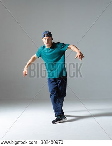 Cool Guy Breakdancer Dancing In Studio Isolated On Gray Background. Breakdance Lessons