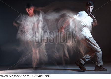 Stylish Young Guy Breakdancer Dancing In Studio On Black Background. Long Exposure Shot. Battle Comp