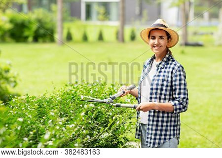 gardening and people concept - happy smiling young woman in straw hat with pruner or pruning shears cutting branches at summer garden