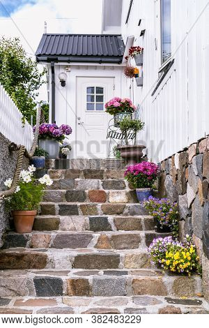 Colorfull Flowers On He Staircase Of A White Wooden House In Scandinavia