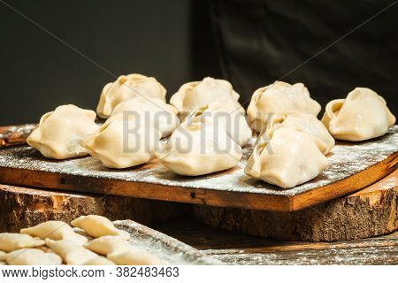 Closeup On Semi-finished Dumplings Manti On The Wooden Board With Flour