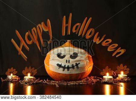 Halloween Pumpkin With Face Drawn On A Disposable Protective Mask Next To Burning Candles On A Black