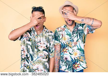 Young gay couple of two men wearing summer hat and hawaiian shirt peeking in shock covering face and eyes with hand, looking through fingers with embarrassed expression.