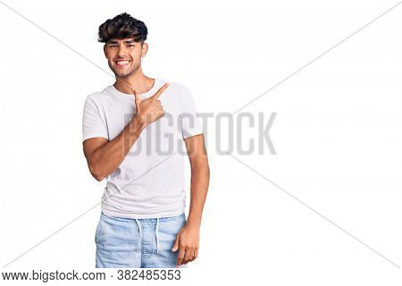 Young hispanic man wearing casual clothes cheerful with a smile of face pointing with hand and finger up to the side with happy and natural expression on face