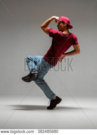 Guy Dancing Contemporary Dance In Studio Isolated On Gray Background. Break Dance Lessons.