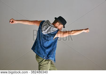 Young Guy Breakdancer In Hat Dancing Hip-hop Like Superman In Studio Isolated On Gray Background. Da