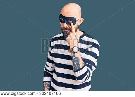Young handsome man wearing burglar mask pointing to the eye watching you gesture, suspicious expression
