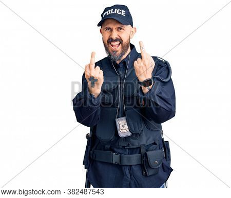 Young handsome man wearing police uniform showing middle finger doing fuck you bad expression, provocation and rude attitude. screaming excited