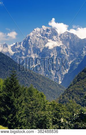 Alpine Mountain Peak Veliki Ozebnik With Few Clouds Surrounded By Hills Of Coniferous Forests. Mount