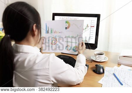 Rear View Of Business Woman Working In Office With Computer Holding Chart Report Paper And Looking.