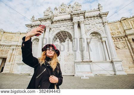 Girl Takes A Selfie In The Square In Front Of Dolmabahce, Istanbul, Turkey. A Young Girl Tourist In