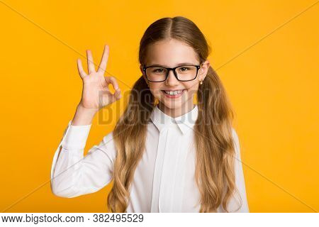 Okay. Cheerful Little School Girl Gesturing Ok Posing Smiling To Camera On Yellow Studio Background.
