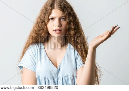 What The Hell Are You Talking About, Nonsense. Studio Shot Of Frustrated Female With Curly Long Hair