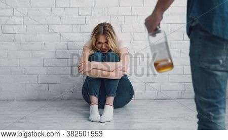 Alcoholism And Domestic Violence. Aggressive Man With Bottle Of Alcohol Threatens Frightened Woman,