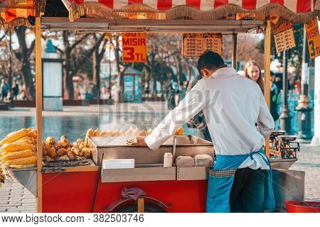 18.12.2019, Istanbul, Turkey. Traditional Street Food. The Corn Seller Stands Behind The Counter Wit