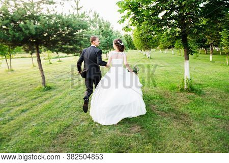 Just Married Couple Running Away In A Green Summer Garden Looking At Each Other. Romantic Married Yo