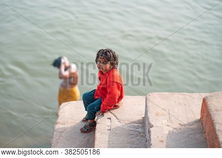 December 17 2019 Varanasi, India. A Dirty Bored Child Sitting On The Steps Near The River. In The Ba