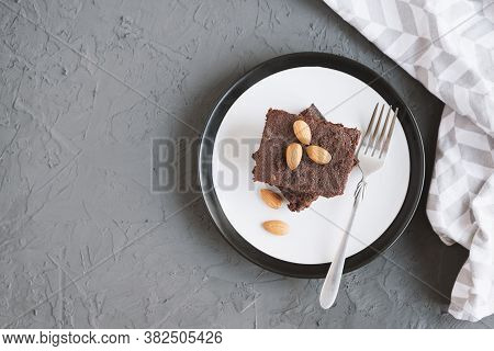 Homemade Chocolate Brownie With Almond Nuts Served On A Plate With Fork And Napkin, Top View