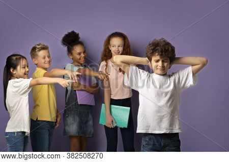 Bullying At Schools Concept. Cruel Schoolkids Harassing Unhappy Little Boy On Lilac Background