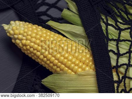 One Bright Yellow Peeled Corn On Cob On A Black Background In Black Shopping Net With Husk Selective