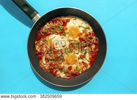 Shakshuka - Poached Eggs In Tomato Sauce, Onion, Pepper And In Iron Pan On Blue Bright Background. F