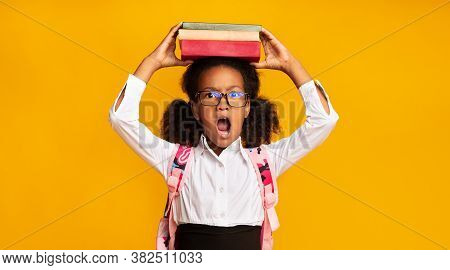 Back-to-school Concept. Discontented African Elementary Student Girl Posing With Books On Head Over