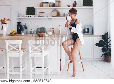 Pretty Woman Drinking Coffee In The Kitchen In The Morning