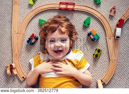 Adorable Happy Redhead Baby Boy Laying On The Carpet Among Railway Tracks And Trains, Wooden Toys