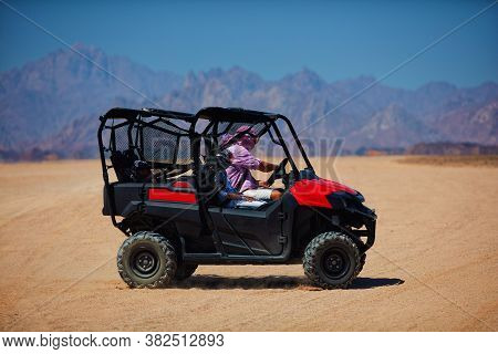 Family Is Driving A Buggy Car Through The Desert. Extreme Tourism Adventures