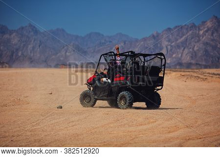 Excited People Are Driving A Buggy Car Through The Desert. Extreme Tourism Adventures
