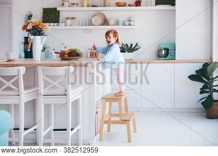 Funny Infant Baby Girl Standing On A Step Stool At The Cozy Kitchen At Home