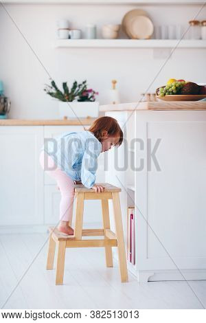 Funny Infant Baby Girl Climbing A Step Stool At The Cozy Kitchen At Home