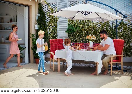 Happy Kids Helping Mother To Lay Up The Table At The Summer Patio, Family Lifestyle